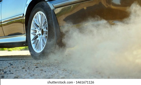 Detail view on wheel of powerful car starting movement and slipping on asphalt road. Small stones and dust flying out from under tire of auto. Vehicle beginning motion. Concept of burnout. Slow motion