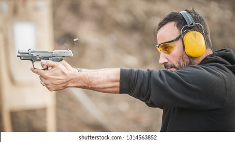 Detail view of shooter holding gun and training tactical shooting, close up. Shooting range