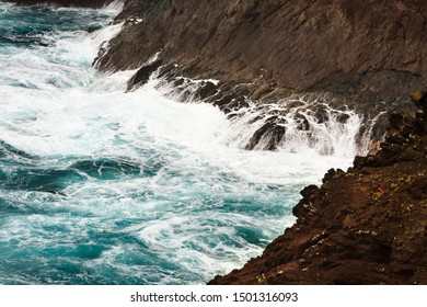 Detail view of tall splashing waves hitting the lava rocks at Playa de Nogales in La Palma, Spain.