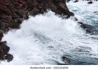 Detail view of tall splashing waves hitting the rocks at Playa de Nogales in La Palma, Spain.