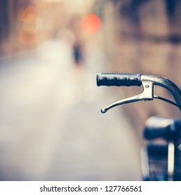 Detail of a Vintage Bicycle Handlebar Resting in the Narrow Street (vintage color toned image)