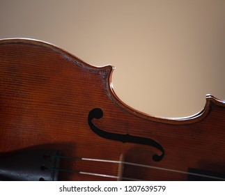 Detail of a viola showing the lower bout and c-curve of the edge of the instrument against a neutral background. One f-hole and some strings can also be seen