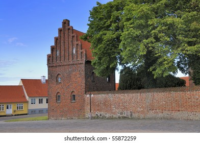 A detail of the Wall around The famous Our Lady?s Church in Kalundborg Denmark, with restored medieval houses in the back.