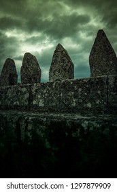 Detail of a  wall with pointy stones against dark cloudy sky