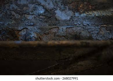 Detail of the weathered and rusting underside of a steel railroad bridge. Image shows peeling paint and rusted steel beams and rivets.
