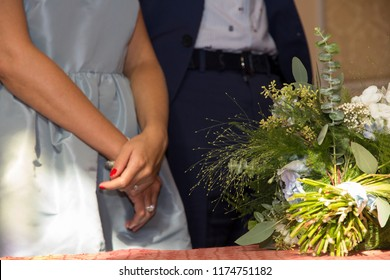 A detail of a wedding couple standing in front of the altar, ready to marry. The bridal bouquet is laying in front of them. The beautiful bride is crossing her arms, visibly showing her shiny ring.