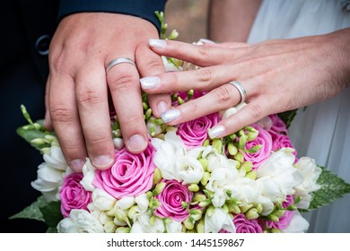Detail of wedding rings in nature with flowers. Closeup of wedding rings.