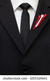 The detail of wedding suit with golf design.Golf tees in the color of Austria flag on the flap of black suit