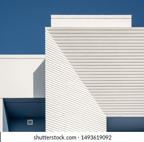 Detail of a white and blue modern villa in a Middle Eastern, high-end, luxury housing development on a sunny day with strong shadows.