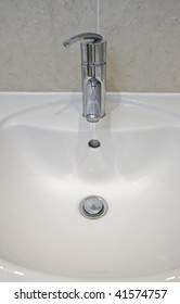 detail of a white ceramic hand wash basin with chrome water mixer tap over