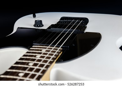 detail of white electric guitar on black background
