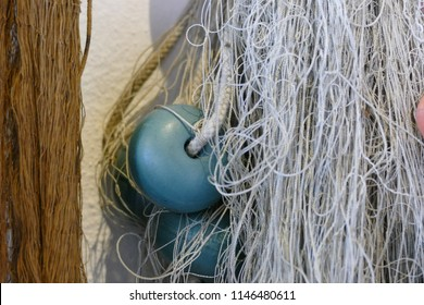 Detail of white fishing net with blue floaters and brown fishing net , Italy, July 2018