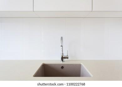 Detail of a white rectangular designer kitchen sink with chrome water tap