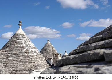 Detail of white round house with specific architecture and stone roof with sign from unesco world heritage Trulli of Alberobello in Italy