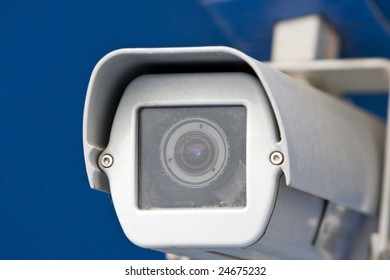 Detail of a white security camera. Isolated on blue background.