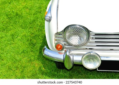 Detail of a white vintage car against green grass background