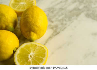 Detail of whole and sliced lemons on the marble table in the kitchen. Citrus rich in vitamin C. With copy space.