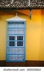 Detail of a window with barrotes, bars constructed of small wooden columns, typically seen in Trinidad, a UNESCO World Heritage Site in central Cuba