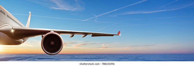Detail of wing of commercial airplane jetliner flying above clouds in beautiful sunset light. Travel and business concept