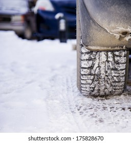 Detail of a winter tire caked with snow
