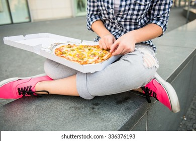 Detail of woman eating pizza outdoor in street