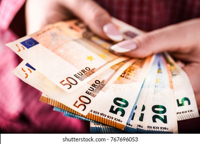 Detail of woman hands with euro money, Euro currency offering , euro bills