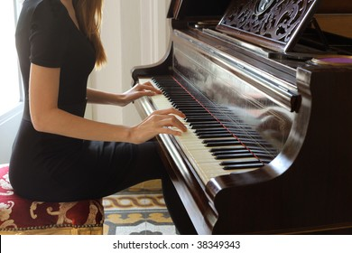 detail of woman hands playing the piano