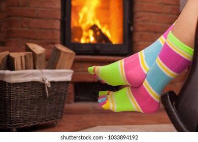 Detail of woman legs in funny socks relaxing in front of fireplace - cozy place concept