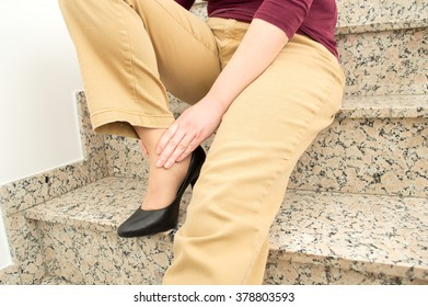 detail of a woman with painful ankle because of falling on stairs