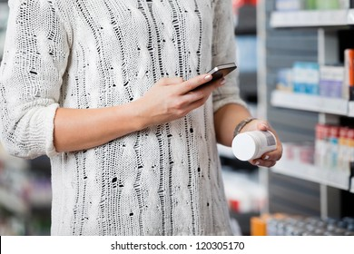 Detail of woman scanning bottle with cell phone in pharmacy