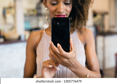 Detail of woman taking a photo with smartphone in a cafe.