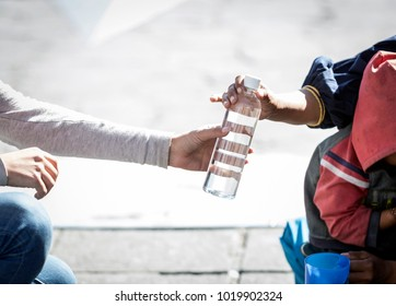 Detail of woman's hand giving a bottle of water to a homeless person