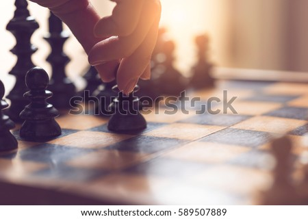 Detail of a woman's hand making the first move in a chess game, moving the pawn one field forward. Selective focus