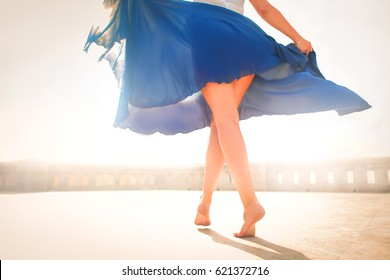 Detail of woman's legs dancing barefoot. She is wearing a blue skirt.