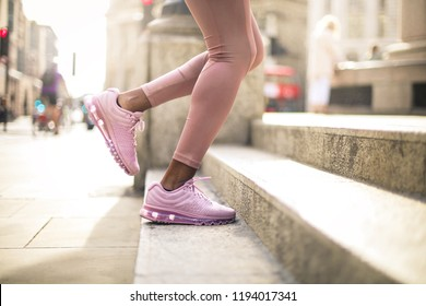 Detail of woman's legs while running on stairs in the street