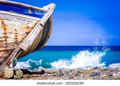 Detail of a wooden shipwreck with turquoise tropical sea background.