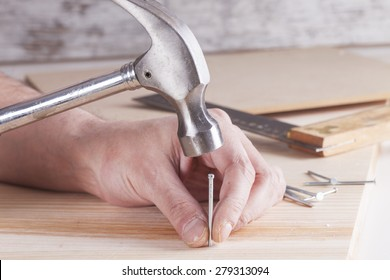detail of worker with a nail and a hammer