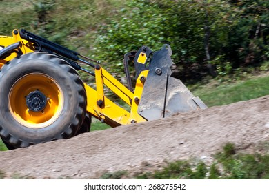 detail yellow excavator traveling on the road, panning image