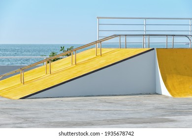 Detail of the yellow ramp skating park with blue sky and grey concrete. Bright architectural element