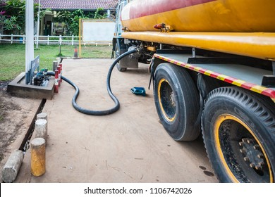 Detail of a yellow tank truck unloading gasoline in a gas station