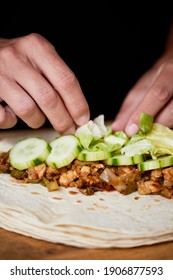detail of a young caucasian man preparing a durum or a burrito, with chicken meat cooked with different vegetables such as onion or red and green pepper, and fresh lettuce and raw cucumber