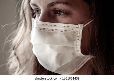 Detail der jungen Kaukasierin mit weißer medizinischer Gesichtsmaske. Konzentrieren Sie sich auf den vorderen Teil des Gesichts, unscharfer Hintergrund. Coronavirus, COVID-19-Quarantäne. Maske als Schutz. Doktor, Krankenpflegekonzept.
