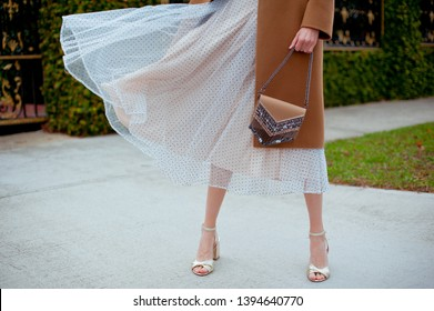 Detail of young fashionable woman wearing beige coat, tulle midi skirt and gold high heels. She holding stylish beige handbag with silver details in hands. Street style.