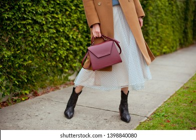 Detail of young fashionable woman wearing beige wool coat, sweater, tulle midi skirt and black high heel cowboy boots. She is holding stylish burgundy handbag in hands. Street style.