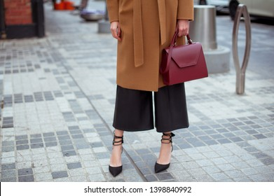 Detail of young fashionable woman wearing beige coat, leather pants and black high heel shoes. She is holding stylish burgundy handbag in hands. Street style.