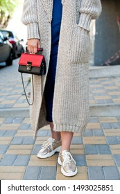 Detail of young fashionable woman wearing beige knit cardigan and midi silk dress. She is holding stylish mini black and red handbag in hands. Street style.