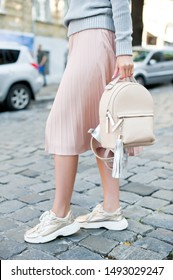 Detail of young fashionable woman wearing grey knit sweater, midi beige skirt and golden sneakers. She is holding stylish beige backpack in hands. Street style.