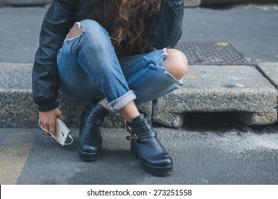 Detail of a young girl in jeans posing in an urban context