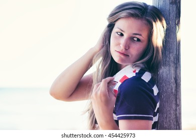 Detail of young girl leaning a wooden column. She has a cute hairstyle. Place for your text.
