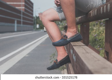 Detail of a young handsome man wearing loafers and posing in an urban context